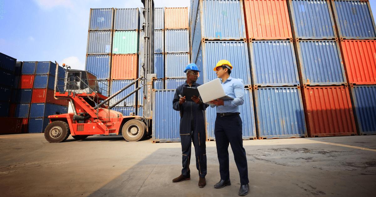 Двама мъже, на товарен док, обсъждат, на фона на контейнери.