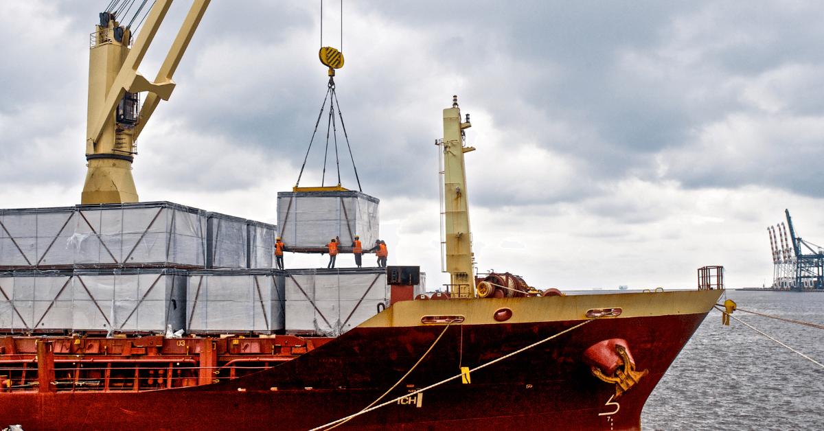 Работници товарят насипен товар на кораб.