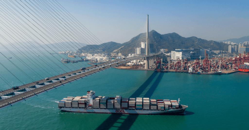 Контейнеровоз навлиза в пристанещен залив на фона голям мост.